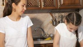 Den skämtsamma mamman och den tonåriga flickan lagar mat tillsammans i köket som suddar sig i mjöl lager videofilmer