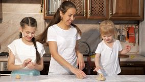 Den skämtsamma mamman och två döttrar lagar mat tillsammans i köket som tillsammans suddar sig i mjöl, rolig tid stock video