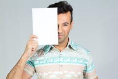 Den skämtsamma mannen täcker halva framsidan med en tom rektangulär kartell Royaltyfria Foton