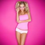 Den skämtsamma unga blondinen modellerar i pigtails Royaltyfri Foto