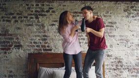 Den skämtsamma den ungdomarmannen och kvinnan dansar på säng som lyssnar till musik och sjunger genom att använda hårtorken och T stock video