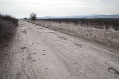 Den skadade asfalttrottoarvägen med gropar som orsakas av frysningen och blidvädret, cyklar under vinter Arkivbild