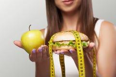 Den skadliga och sunda äta unga flickan väljer mellan skadlig Royaltyfri Fotografi
