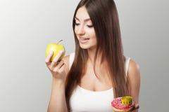 Den skadliga och sunda äta unga flickan väljer mellan skadlig Royaltyfria Bilder