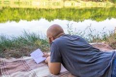 Den skalliga grabben skriver i en anteckningsbok i gräset på en filt och tänker av drömmarna nära sjösommarsolen Arkivfoton