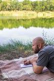 Den skalliga grabben skriver i en anteckningsbok i gräset på en filt och tänker av drömmarna nära sjösommarsolen Royaltyfri Fotografi