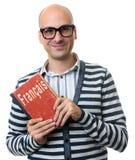 Den skalliga mannen rymmer en lärobok Lära franskt begrepp arkivfoton