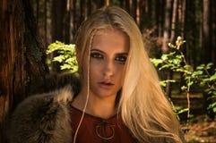 Den skandinaviska flickan med runic undertecknar in ett trä Arkivbild