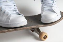Den Skateboarding personen står med fot ifrån varandra på en gammal skateboard Arkivbild