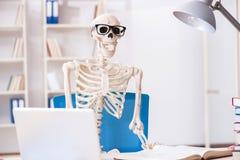 Den skelett- affärsmannen som arbetar i kontoret Fotografering för Bildbyråer