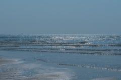 Den skinande vändkretshavsvågen på blått sätter på land sand Arkivbild