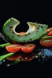 Den skivade avokadot, halfs av körsbärsröda tomater och gräslökar på den svarta reflekterande yttersidan med frö och saltar smulo arkivfoton