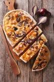Den skivade pajen flammkuchen på tabellen Vertikal bästa sikt Royaltyfria Foton