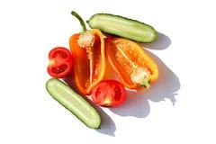 Den skivade röda gröna gula apelsinen för för för grönsakgurkor, spanska peppar och tomater i vattendroppar på vit bakgrund isole royaltyfri fotografi