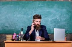 Den skolarektorn eller läraren som kallar föräldrar för att anmäla om examen, resulterar Skolaläraren att bry sig om kommunikatio royaltyfri foto