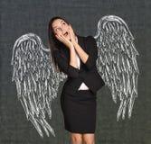 Den skrämda flickan med vingar målade på väggen Royaltyfri Bild