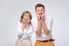 Den skrämde mannen och kvinnan som att bita som är deras, spikar känsla, belastade och förvånade royaltyfria foton