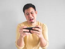 Den skriande mannen förlorar den mobila leken arkivfoto