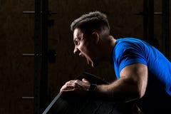 Den skrikiga idrottsmankroppsbyggaren lyfter ett tungt tungt hjul, slut arkivfoton