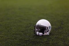 Den skyddande vita hjälmen för leken av amerikansk rugby ligger på det gröna gräset på sportfältet arkivfoto