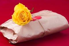 Den slågna in gåvan och steg på en röd bakgrund Fotografering för Bildbyråer