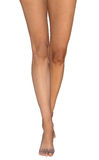 Den slanka barfota brunbrända kvinnlign lägger benen på ryggen anseende på tår Royaltyfri Foto
