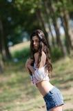 Den slanka brunettdamen med långt hår som spelar med hennes skjorta och, avslöjer henne den plana buken Fotografering för Bildbyråer
