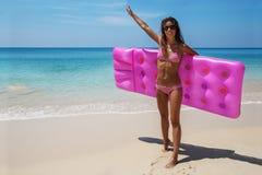 Den slanka brunettkvinnan solbadar med en luftmadrass royaltyfri bild