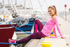 Den slanka flickan i sportar bär att vila efter övningen i hamnstad, sund aktiv livsstil Royaltyfria Bilder