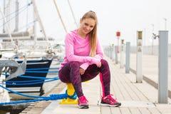 Den slanka flickan i sportar bär att vila efter övningen i hamnstad, sund aktiv livsstil royaltyfri bild