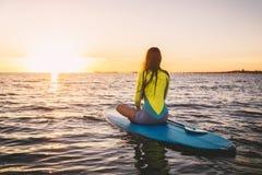 Den slanka flickan står på upp skovelbrädet på ett tyst hav med sommarsolnedgångfärger Koppla av i havet Royaltyfri Bild