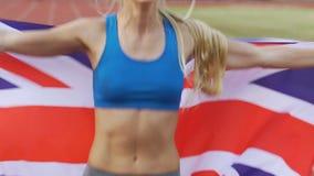 Den slanka idrottskvinnabanhoppningen och hållande UK sjunker och att fira hennes seger i strid lager videofilmer