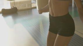 Den slanka kroppen av den unga damen som gör repet som hoppar over i solig idrottshall arkivfilmer