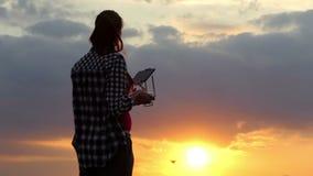 Den slanka kvinnan fungerar en panel för att kontrollera ett surr på solnedgången stock video