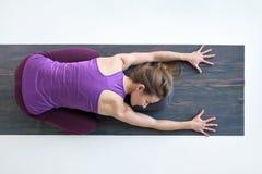 Den slanka kvinnan som gör yoga för rygg och att vila att ligga i barn, poserar, Balasana ställing arkivfoton