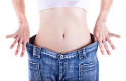 Den slanka kvinnan visar henne att väga förlust genom att ha på sig jeans arkivbilder