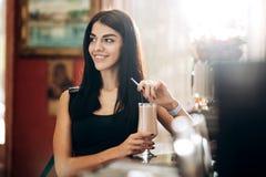 Den slanka nätta flickan står bredvid stång i konditionklubban och håller ett exponeringsglas med coctailen i hennes hand fotografering för bildbyråer
