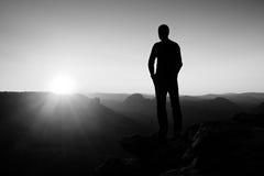 Den slanka turisten på klippan vaggar in väldear parkerar håller ögonen på över den dimmiga och dimmiga morgondalen till solen Arkivbild