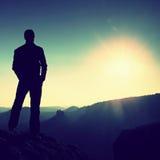 Den slanka turisten på korsmaximum av det steniga berget håller ögonen på över den dimmiga och dimmiga morgondalen till solen Royaltyfria Foton