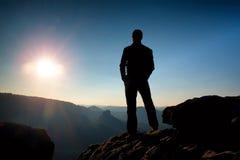 Den slanka turisten på korsmaximum av det steniga berget håller ögonen på över den dimmiga och dimmiga morgondalen till solen Arkivbild