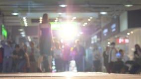 Den slanka yrkesmässiga modellen i svart klänning på höga häl befläcker podiet i panelljus under en modeshow stock video
