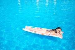 Den Sleppy flickan ligger på den iar madrassen och att kyla Hon får någon solbränna Den unga kvinnan är i mitt av simbassängen arkivbilder