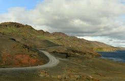 Den slingriga vägen bland bergen på sjön Dramatiskt väder iceland royaltyfria foton