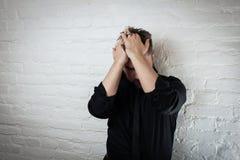 Den slog ned mannen rymmer hans huvud, som han lider från fördjupning och fel Använd det för en huvudvärk, ett pengarproblem elle arkivbild