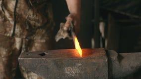 Den Slowmotion closeuphovslagaren räcker manuellt att förfalska varm metall på städet i smedja med gnistafyrverkerier arkivfilmer
