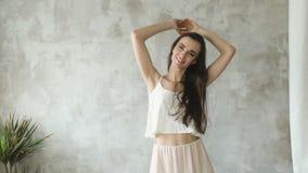 Den Slowmotion härliga sexiga flickan poserar in i kamera och smililng Modellprov i studio arkivfilmer