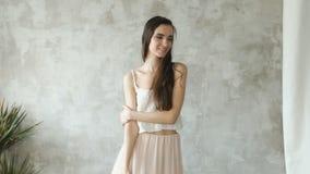 Den Slowmotion härliga sexiga flickan poserar in i kamera och smililng Modellprov i studio lager videofilmer