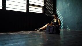 Den Slowmotion panorera unga kvinnan för passformen med sportar hänger löst att sitta på golv, och slå in handen med förbinda stock video