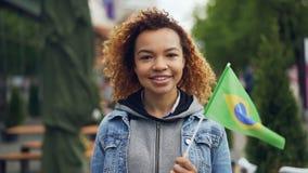 Den Slowmotion ståenden av den gladlynta afrikansk amerikanflickan som ser kameran och det hållande brasilianska flaggaanseendet  stock video