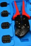 Den slutliga krusa pressplattången som förläggas i blått plast- fall med utbytbart, dör för olika kabeldiametrar Royaltyfria Foton